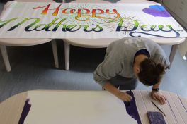 A woman in prison paints Mother's Day posters