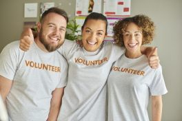 Three people stand together each wearing a T-shirt with volunteer printed on the front